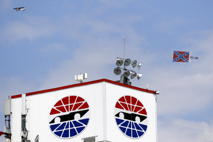 A plane pulls a Confederate battle flag over Bristol Motor Speedway before the NASCAR All-Star auto race in Bristol, Tenn, Wednesday, July 15, 2020. (AP Photo/Mark Humphrey)