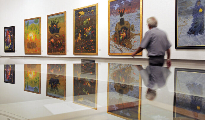 FILE - In this Tuesday, June 22, 2010 file photo q man walks in front of Arik Brauer's paintings at the exhibition 'Fantastic Art from Vienna' in the Panorama museum in Bad Frankenhausen, central Germany. Austrian-Israeli artist Arik Brauer, known for his colorful and surreal paintings and murals, has died at the age of 92. Austrian public broadcaster ORF reported Monday that Brauer died late Sunday, Jan 24, 2021 surrounded by his family. It gave no cause of death. (AP Photo/Jens Meyer, file)