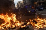 Spanish police vans drive next to burning barricades during clashes with Catalan pro-independence protestors in Barcelona, Spain, Friday, Oct. 18, 2019.The Catalan regional capital is bracing for a fifth day of protests over the conviction of a dozen Catalan independence leaders. Five marches of tens of thousands from inland towns are converging in Barcelona's center for a mass protest. (AP Photo/Bernat Armangue)