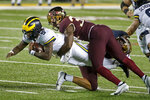 Michigan quarterback Joe Milton (5) leaps forward as Minnesota defensive lineman Boye Mafe (34) tackles him in the second quarter of an NCAA college football game Saturday, Oct. 24, 2020, in Minneapolis. (AP Photo/Bruce Kluckhohn)