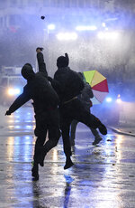 """Left-wing demonstrators throw stones at a water cannon during riots in Leipzig, Germany, Saturday, Sept. 18, 2021. The campaign alliance """"We are all Linx"""" had mobilized nationwide for the demonstration. (Jan Woitas/dpa via AP)"""