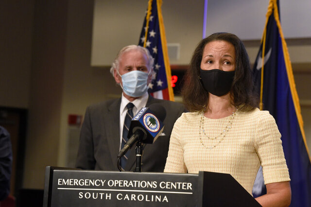 South Carolina Gov. Henry McMaster, left, looks on as state epidemiologist Linda Bell, right, speaks during a COVID-19 briefing on Wednesday, July 29, 2020, in West Columbia, S.C. As of Monday, McMaster says all businesses will be allowed to be open, as long as they adhere to social distancing and capacity limits. (AP Photo/Meg Kinnard)