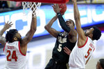 Purdue guard Brandon Newman, center, goes up for a shot against Maryland guard Eric Ayala, right, and forward Donta Scott during the first half of an NCAA college basketball game, Tuesday, Feb. 2, 2021, in College Park. (AP Photo/Julio Cortez)