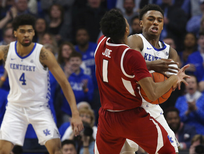 Kentucky's Ashton Hagans, right, fouls Arkansas' Isaiah Joe (1) as Kentucky's Nick Richards (4) watches during the second half of an NCAA college basketball game in Lexington, Ky., Tuesday, Feb. 26, 2019. Kentucky won 70-66. (AP Photo/James Crisp)