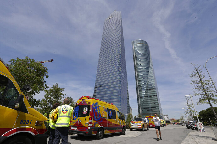 Ambulances wait outside the Torrespacio skyscraper, right, as a jogger runs by in Madrid, Spain, Tuesday, April 16, 2019, after the 57-storey office tower in Madrid's business district that houses several foreign embassies was evacuated due to an unspecified security threat. Staff at the Torrespacio skyscraper received around midday on Tuesday a phone call with the threat, a spokeswoman with the National Police said, prompting the tower's own security personnel to evacuate the building.(AP Photo/Paul White)