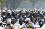 Brazil's President Jair Bolsonaro, center, takes part in a caravan of motorcycle enthusiasts who gathered in a show of support for Bolsonaro, in Sao Paulo, Brazil, Saturday, June 12, 2021. (AP Photo/Marcelo Chello)