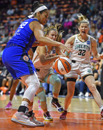Connecticut Sun center Brionna Jones, left, and New York Liberty's Sabrina Ionescu, center, and Sami Whitcomb (32) vie for the ball during the first half of a WNBA basketball game Wednesday, Sept. 15, 2021, in Uncasville, Conn. (Sean D. Elliot/The Day via AP)