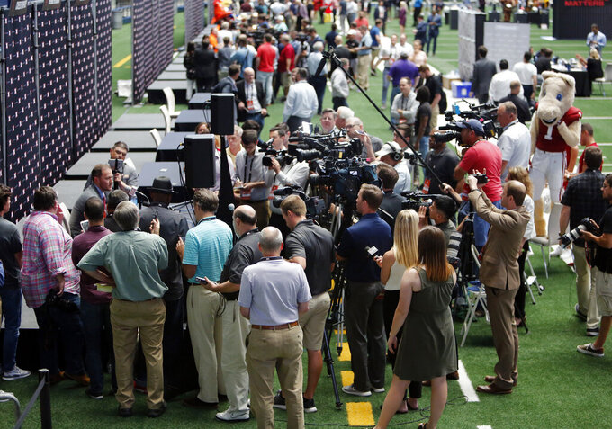 Reporters crowd around player and coach interview stations on the first day of Big 12 NCAA college football media days Monday, July 15, 2019, at AT&T Stadium in Arlington, Texas. (AP Photo/David Kent)