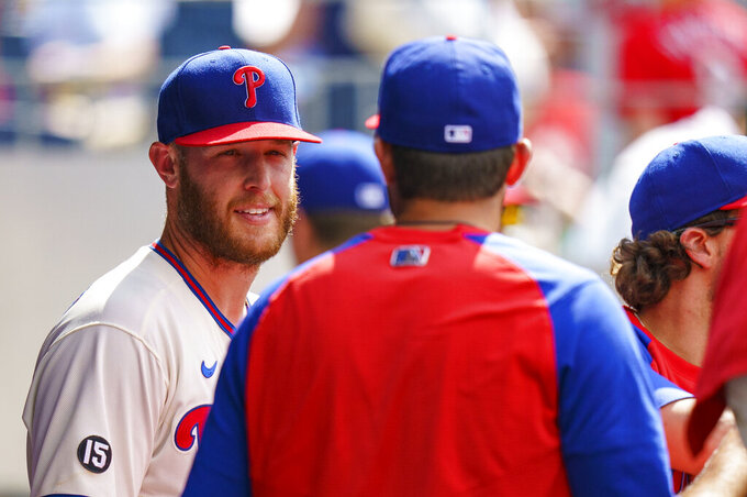 Philadelphia Phillies' Zack Wheeler, left, talks with a teammate after getting pulled during the eighth inning of a baseball game against the Boston Red Sox, Sunday, May 23, 2021, in Philadelphia.  (AP Photo/Chris Szagola)