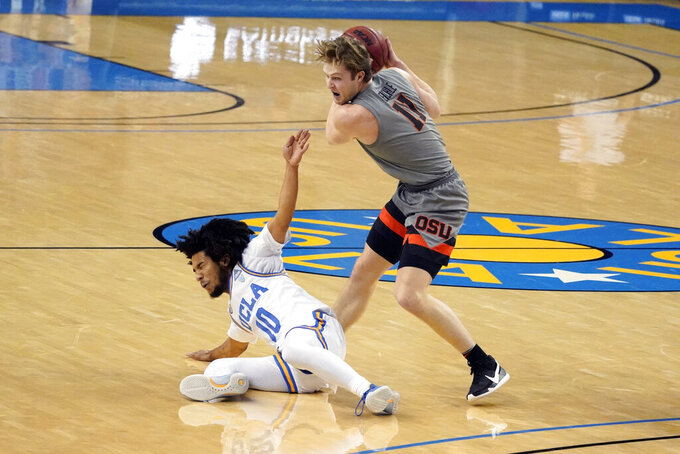 Oregon State guard Zach Reichle, right, grabs a rebound over UCLA guard Tyger Campbell (10) during the first half of an NCAA college basketball game Saturday, Jan. 30, 2021, in Los Angeles. (AP Photo/Marcio Jose Sanchez)