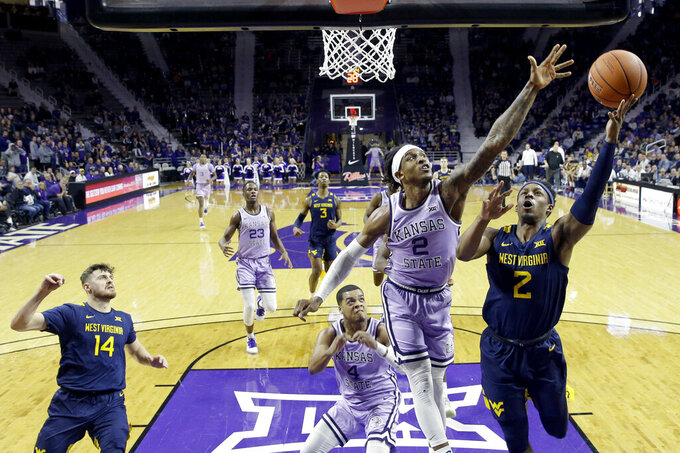 West Virginia's Brandon Knapper (2) shoots under pressure from Kansas State's Cartier Diarra (2) during the first half of an NCAA college basketball game Saturday, Jan. 18, 2020, in Lawrence, Kan. (AP Photo/Charlie Riedel)
