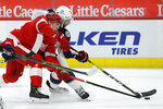 Detroit Red Wings defenseman Troy Stecher, left, battles Columbus Blue Jackets defenseman Seth Jones for the puck during the first period of an NHL hockey game Tuesday, Jan. 19, 2021, in Detroit. (AP Photo/Duane Burleson)