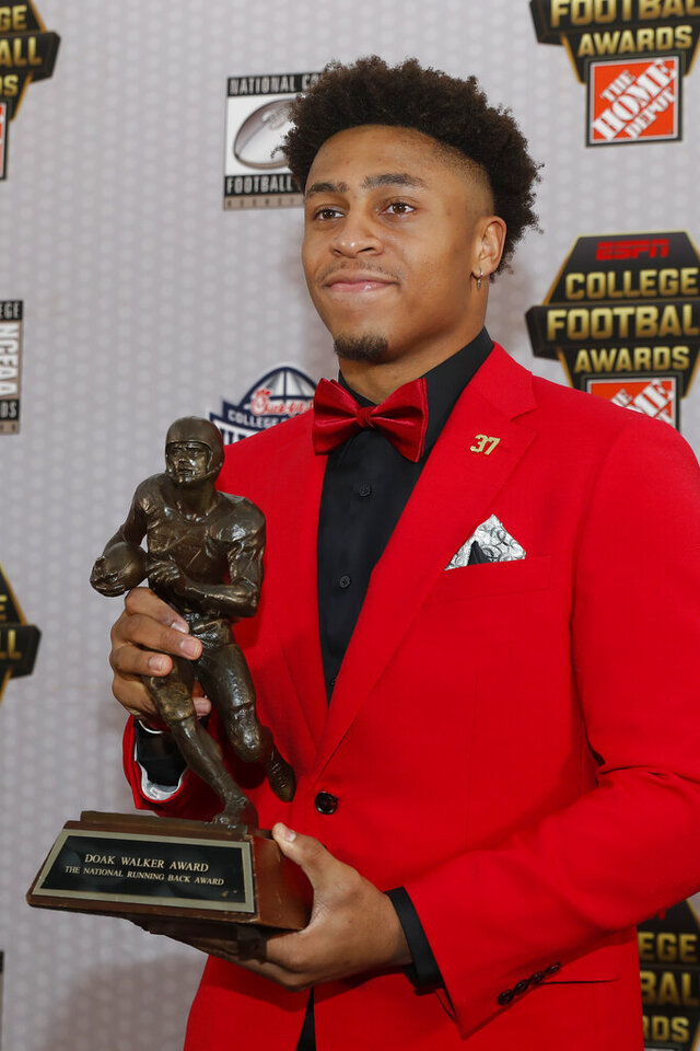 Wisconsin's Jonathan Taylor poses with trophy after winning the Doak Walker Award for being the nation's best running back Thursday, Dec. 12, 2019, in Atlanta. (AP Photo/John Bazemore)