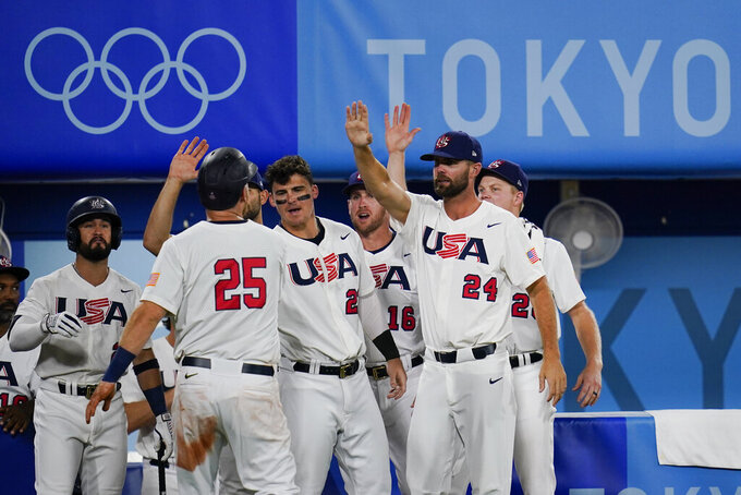 United States' Todd Frazier (25) celebrate with teammates after scoring on a hit by Mark Kolozsvary during a semi-final baseball game at the 2020 Summer Olympics, Thursday, Aug. 5, 2021, in Yokohama, Japan. (AP Photo/Sue Ogrocki)
