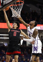 Rutgers guard Geo Baker, left, drives to the basket against Northwestern forward Vic Law during the first half of an NCAA college basketball game, Wednesday, Feb. 13, 2019, in Evanston, Ill. (AP Photo/Nam Y. Huh)