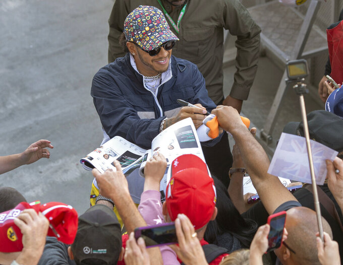 Mercedes driver Lewis Hamilton, of Great Britain, signs autographs during the open house day for the Formula One Canadian Grand Prix auto race in Montreal, Thursday, June 6, 2019. (Ryan Remiorz/The Canadian Press via AP)