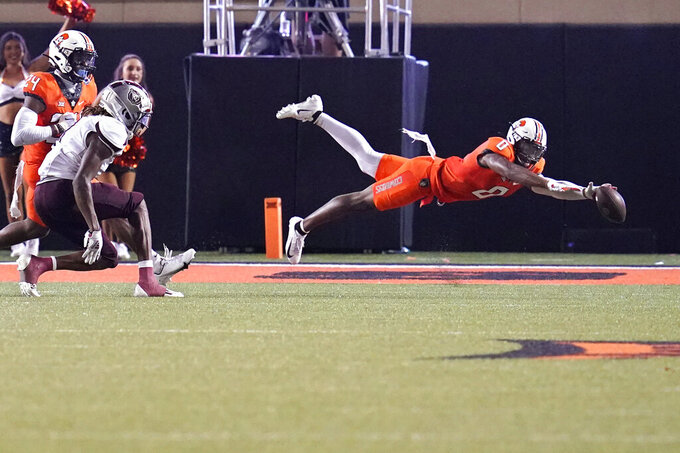 Oklahoma State cornerback Christian Holmes (0) reaches for the ball on an incomplete pass intended for Missouri State wide receiver Xavier Lane, left, in the second half of an NCAA college football game, Saturday, Sept. 4, 2021, in Stillwater, Okla. (AP Photo/Sue Ogrocki)