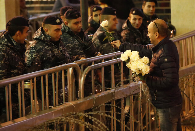 An anti-government protester gives flowers to the riot police, during ongoing protests against the ruling elite of corruption and financial crisis, in downtown Beirut, Lebanon, Wednesday, Dec. 18, 2019. Lebanon's caretaker prime minister said Wednesday he's no longer a candidate for the post, eliminating himself from consideration on the eve of scheduled consultations between the president and parliamentary blocs for naming a new premier. (AP Photo/Hussein Malla)