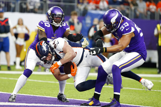 Denver Broncos tight end Troy Fumagalli, center, catches a 3-yard touchdown pass between Minnesota Vikings defenders Mackensie Alexander, left, and Anthony Barr, right, during the first half of an NFL football game, Sunday, Nov. 17, 2019, in Minneapolis. (AP Photo/Bruce Kluckhohn)