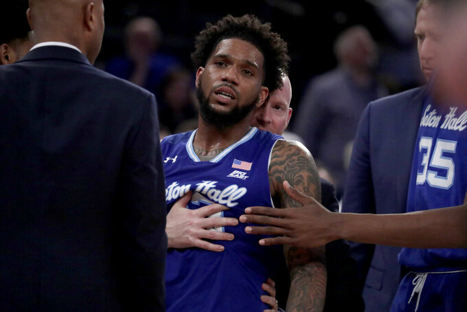 Seton Hall guard Myles Powell, front, is held by head coach Kevin Willard, back, after an argument with Marquette players during the second half of an NCAA college basketball semifinal game in the Big East men's tournament, Friday, March 15, 2019, in New York. Seton Hall won 81-79. (AP Photo/Julio Cortez)