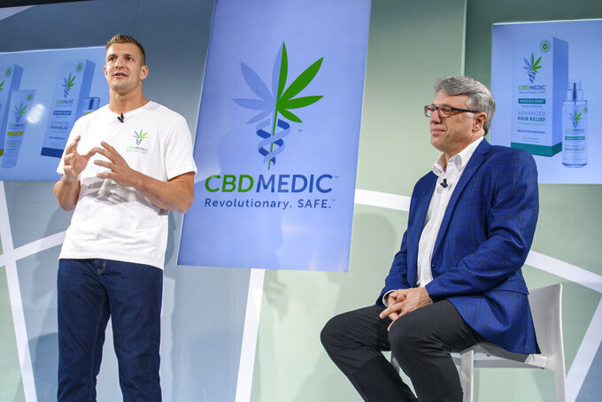FILE - In this Aug. 27, 2019, file photo, former New England Patriots tight end Rob Gronkowski, left, speaks as Perry Antelman, CEO of Abacus Health Products, listens during a news conference announcing in New York.  The home of the New England Patriots has a new sponsorship deal with Abacus Health Products that will put the cannabidiol company's hemp leaf logo on a water tower looming over the stadium and on a sign overlooking an entrance.  (AP Photo/Corey Sipkin, File)