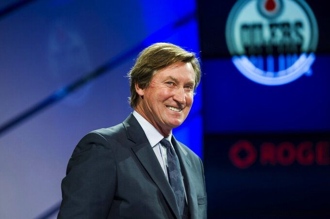 FILE - In this Dec. 10, 2017, file photo, former Edmonton Oilers great Wayne Gretzky speaks to media about the upcoming NHL Centennial Greatest Team celebration hockey game and being voted the greatest team of all time in Toronto. Possibly losing as many as 13 games with the NHL on hold because of the coronavirus pandemic could leave Alex Ovechkin two short of another 50-goal season and threaten his ability to break Gretzky's all-time record. (Christopher Katsarov/The Canadian Press via AP, File)