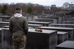 A young man stands in front of the Holocaust Memorial after he laid down a red rose on a slab of the memorial to commemorate the victims of the Nazis in Berlin, Sunday, Jan. 27, 2019. The International Holocaust Remembrance Day marks the liberation of the Auschwitz Nazi death camp on Jan. 27, 1945. (AP Photo/Markus Schreiber)