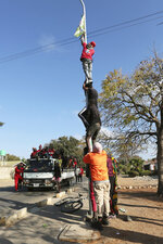 Supporters of Zambian opposition leader Hakainde Hichilema remove campaign posters of Zambian President Edgar Lungu from street poles in Lusaka, Zambia, Monday Aug, 16, 2021.  Hichilema has won the southern African country's presidency after taking more than 50% of the vote. (AP Photo/Tsvangirayi Mukwazhi)
