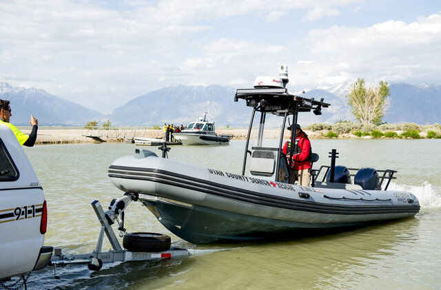 "In this May 14, 2020 photo, members of the search team load a boat onto a trailer as authorities examine the body of one of the two Saratoga Springs teenagers that went missing in Utah Lake at the Lincoln Beach Marina west of Spanish Fork, Utah.  The family and friends of two Saratoga Springs teenagers who drowned in Utah Lake after a catastrophic windstorm hit the area in May are proposing building a ""life jacket loaner station"" to prevent similar accidents from happening in the future.  (Isaac Hale/The Daily Herald via AP)"