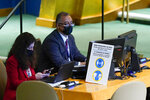 United Nations employees work at a desk with a sign informing the coronavirus protocols during the 76th Session of the United Nations General Assembly, Tuesday, Sept. 21, 2021 at U.N. headquarters. (AP Photo/Mary Altaffer, Pool)