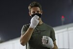 Haas driver Romain Grosjean of France arrives to the paddock to thank the marshals, Thursday, Dec. 3, 2020, in Bahrain International Circuit in Sakhir, Bahrain.  Grosjean, escaped with only minor burns when his Haas car exploded into a fireball after crashing on the first lap at last weekend's Bahrain GP. (AP Photo/Kamran Jebreili)