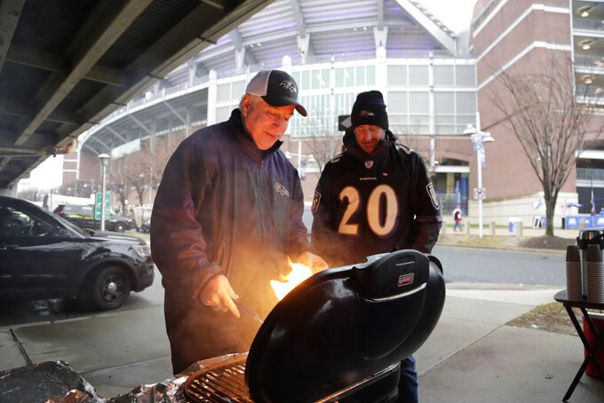 Allen Schiff grilling burgers while tailgating in the parking lot before the start of an NFL football game between the Baltimore Ravens and the San Francisco 49ers, Sunday, Dec. 1, 2019, in Baltimore, Md. (AP Photo/Julio Cortez)
