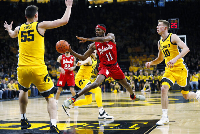 Nebraska guard Dachon Burke Jr. (11) drives to the basket between Iowa's Luka Garza (55) and Joe Wieskamp (10 during the first half of an NCAA college basketball game, Saturday, Feb. 8, 2020, in Iowa City, Iowa. (AP Photo/Charlie Neibergall)