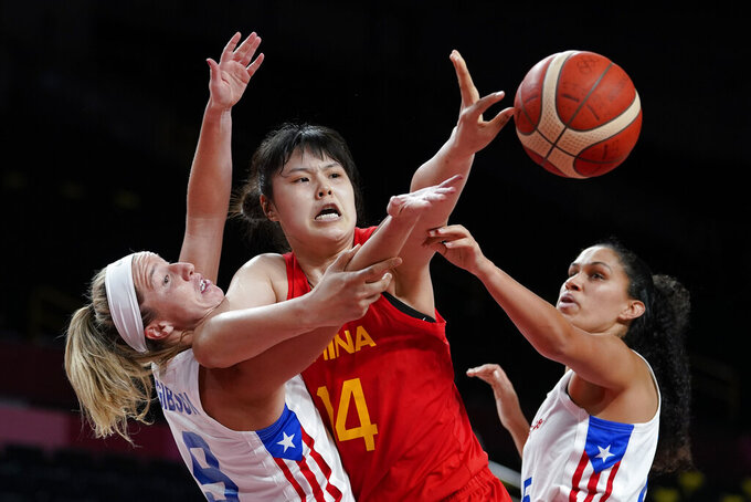 China's Yueru Li (14) and Puerto Rico's Ali Gibson (9) battle for the ball as Isalys Quinones (25) reaches during a women's basketball preliminary round game at the 2020 Summer Olympics in Saitama, Japan, Tuesday, July 27, 2021. (AP Photo/Charlie Neibergall)