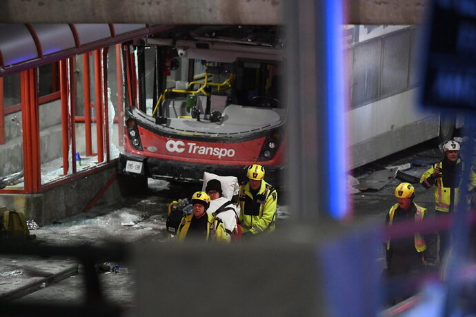 Police and a first responders work at the scene where a double-decker city bus struck a transit shelter in Ottawa, on Friday, Jan. 11, 2019. (Justin Tang/The Canadian Press via AP)