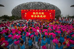 FILE - In this Friday, July 31, 2015 file photo, participants celebrate following the announcement that Beijing will host the 2022 Winter Olympics at a gathering outside of the Beijing Olympic Stadium, also known as the Birds Nest, in Beijing. The sign reads