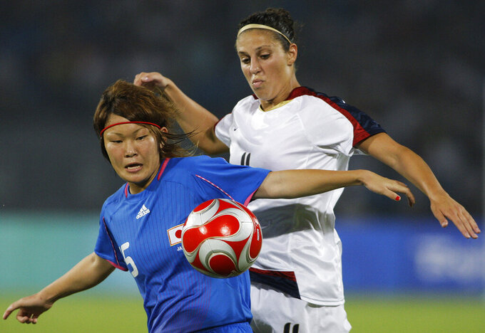 FILE - In this Aug. 18, 2008, file photo, Carli Loyd, right, of the U.S., vies for the ball with Mizuho Sakaguchi, of Japan, during the Beijing 2008 Olympics women semifinals soccer match in Beijing. Older Olympians will be proving that age is just a number in Tokyo. Lloyd is going to be 39 when she plays for the U.S. women's soccer team, but she's not even the oldest soccer player competing this summer. Formiga, who plays for Brazil, is 43. (AP Photo/Petr David Josek, File)