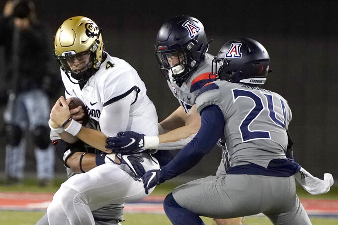 Colorado quarterback Sam Noyer (4) is sacked by Arizona defensive back Isaiah Mays, back left, and Rhedi Short (24) in the first half during an NCAA college football game, Saturday, Dec. 5, 2020, in Tucson, Ariz. (AP Photo/Rick Scuteri)