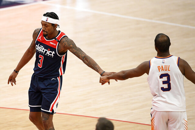 Washington Wizards guard Bradley Beal, left, and Phoenix Suns guard Chris Paul, right, tap hands during the second half of an NBA basketball game, Monday, Jan. 11, 2021, in Washington. (AP Photo/Nick Wass)