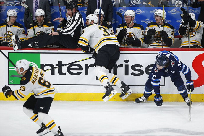 Winnipeg Jets' Mark Scheifele (55) looks over after a check by Boston Bruins' Zdeno Chara (33) during the first period of an NHL hockey game Friday, Jan. 31, 2020, in Winnipeg, Manitoba. (John Woods/The Canadian Press via AP)
