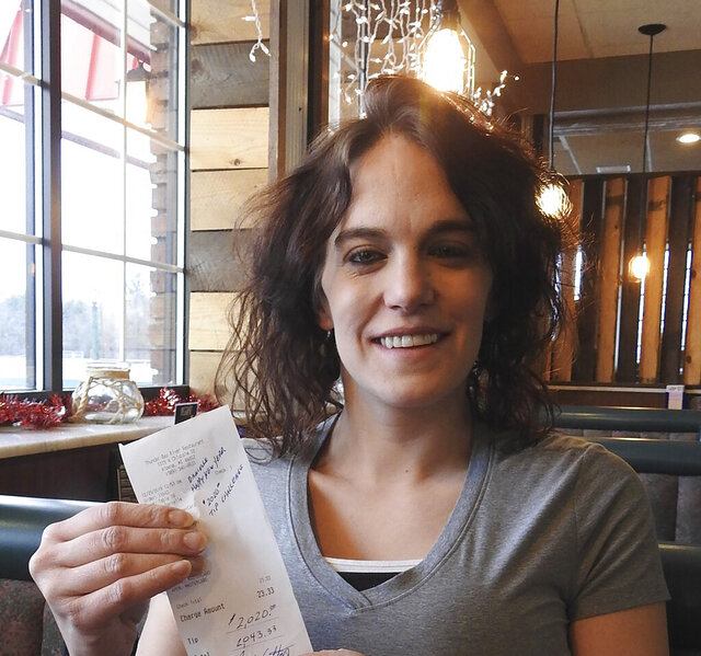 In this Dec. 30, 2019 photo, server Danielle Franzoni holds a receipt from a customer with a $2,020 tip included at Thunder Bay River Restaurant in Alpena, Mich. The credit card receipt said