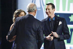 FILE - In this Dec. 5, 2019, file photo, driver Kyle Busch, right, receives his championship ring from NASCAR CEO Jim France, center, at the NASCAR Cup Series Awards in Nashville, Tenn. Two months removed from that second title, Busch is confident _ adamant almost _ that he will close his career at minimum tied with greats Richard Petty, Dale Earnhardt and Jimmie Johnson. (AP Photo/Mark Humphrey, File)