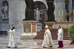 Pope Francis, center, arrives to attend a Mass for Holy Thursday, inside St. Peter's Basilica at the Vatican, Thursday, April 9, 2020. Francis celebrated the Holy Week Mass in St. Peter's Basilica, which was largely empty of faithful because of restrictions aimed at containing the spread of COVID-19. The new coronavirus causes mild or moderate symptoms for most people, but for some, especially older adults and people with existing health problems, it can cause more severe illness or death.  (Alessandro Di Meo/Pool Photo via AP)