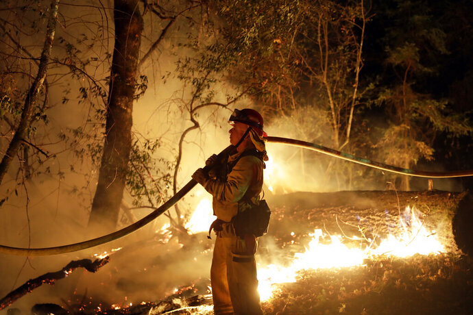 FILE - In this Saturday, Oct. 14, 2017 file photo, a firefighter holds a water hose while fighting a wildfire, in Santa Rosa, Calif. New California data shows insurance companies declined to renew nearly 350,000 home insurance policies in areas at high risk for wildfire since the state began collecting data in 2015. Insurance officials say many people likely found coverage elsewhere, though potentially at higher cost. (AP Photo/Marcio Jose Sanchez, File)