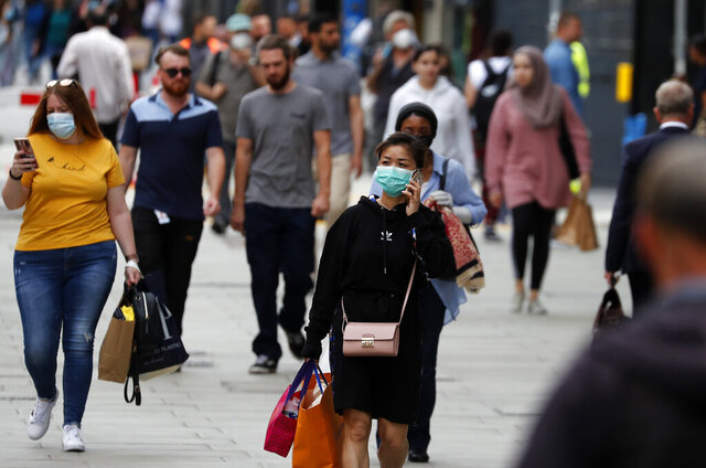 Shoppers walk along Oxford Street in London, Tuesday, July 14, 2020.Britain's government is demanding people wear face coverings in shops as it has sought to clarify its message after weeks of prevarication amid the COVID-19 pandemic. (AP Photo/Frank Augstein)