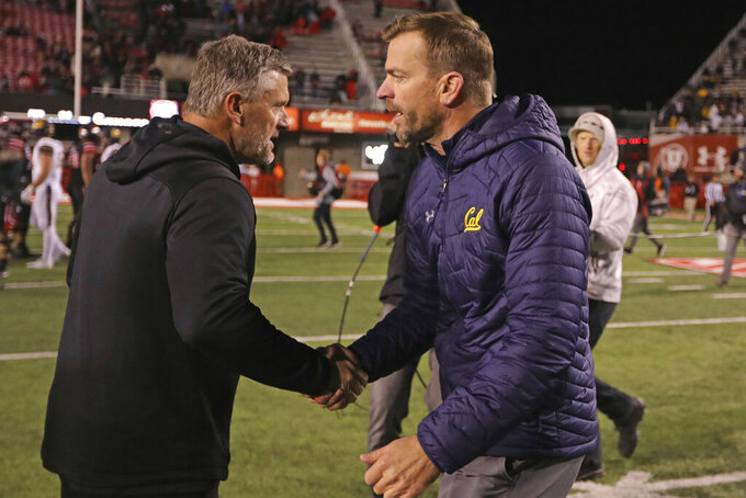 California head coach Justin Wilcox, right, shakes hands with Utah head coach Kyle Whittingham following their NCAA college football game Saturday, Oct. 26, 2019, in Salt Lake City. (AP Photo/Rick Bowmer)