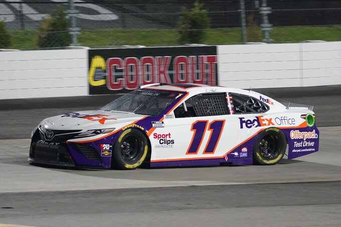 Denny Hamlin (11) leads the field in Turn 2 prior to a rain delay in the NASCAR Cup Series auto race at Martinsville Speedway in Martinsville, Va., Saturday, April 10, 2021. (AP Photo/Steve Helber)