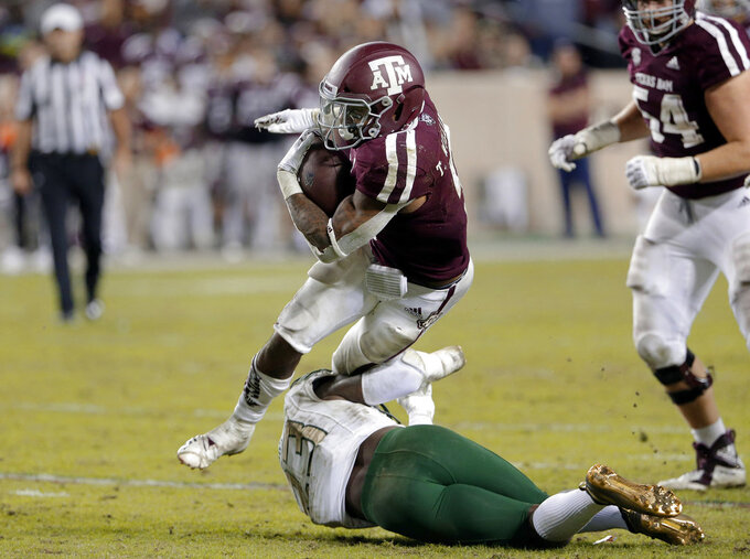 Texas A&M running back Trayveon Williams, top, is caught by UAB safety Mar'Sean Diggs (23) during the second half of an NCAA college football game Saturday, Nov. 17, 2018, in College Station, Texas. (AP Photo/Michael Wyke)