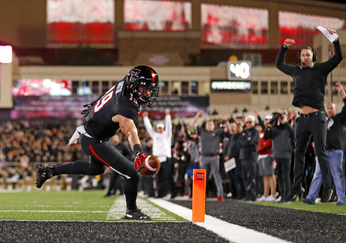 Texas Tech's Zach Austin (19) scores a touchdown during the second half of the team's NCAA college football game against Oklahoma, Saturday, Nov. 3, 2018, in Lubbock, Texas. Texas Tech coach Kliff Kingsbury is at right. (AP Photo/Brad Tollefson)