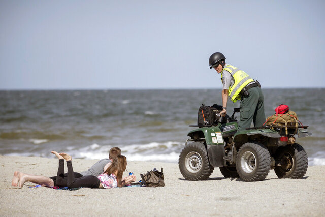 Georgia Department of Natural Resources Law Enforcement Division Corporal Barry Britt, right, enforces Gov. Bryan Kemp's order to open the beaches on Tybee Island, Ga., Saturday, April 4, 2020, allowing people to exercise outside, with social distancing of at least six feet because of the coronavirus outbreak. (Stephen B. Morton/Atlanta Journal-Constitution via AP)